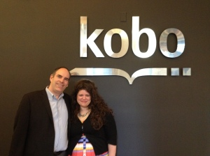 Mark and Rainbow posing in front of the large Kobo logo